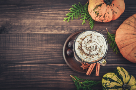 Pumpkin spice latte with whipped cream on wooden background, top view Фото со стока