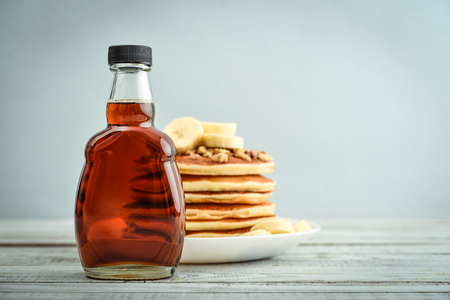 Maple syrup in glass bottle with pancakes on wooden background Imagens