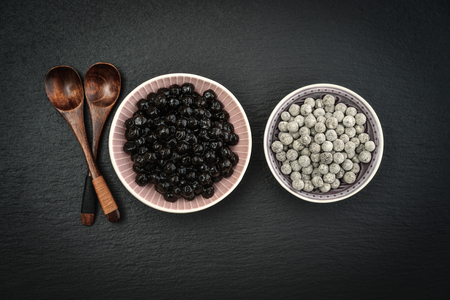 Boiled and Raw Tapioca Pearls in plates on black slate background. For Bubble tea concepts.