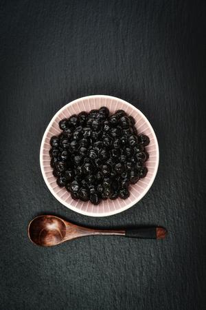 黒いスレート背景に茹でたタピオカ。バブル紅茶の概念。