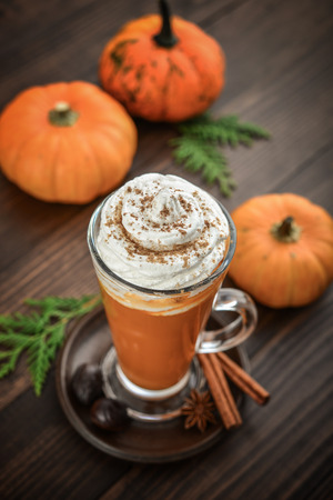 Pumpkin spice latte with whipped cream on wooden background
