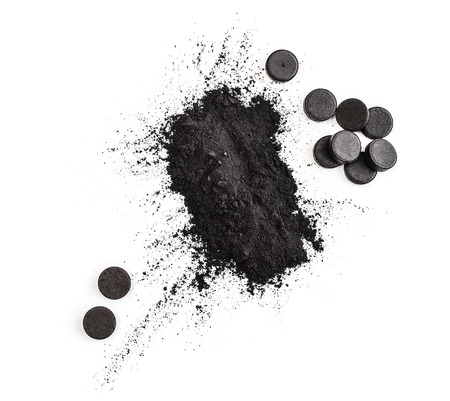 Activated charcoal in powder and in pills isolated on white background