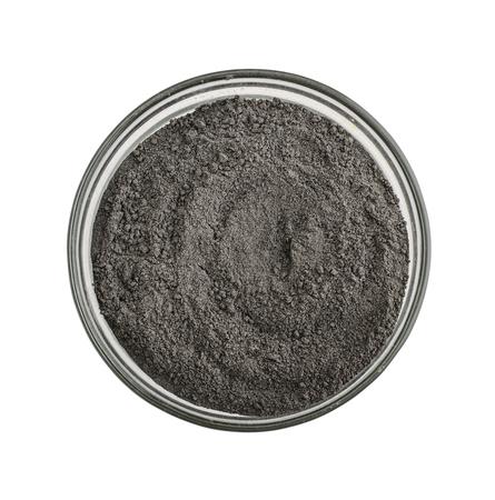 흰색 배경에 고립 된 유리 그릇에 검은 화장품 점토 가루, 스톡 콘텐츠
