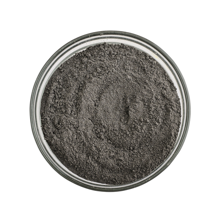 Black cosmetic clay powder in glass bowl isolated on white background,