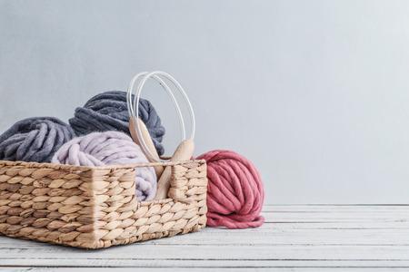 Balls of  super chunky merino woolen yarn with needles in rustic  basket on light blue background. Foto de archivo