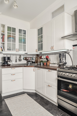 Interior of the kitchen in Scandinavian style with white furniture and a dining table.  Archivio Fotografico