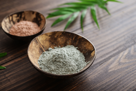 Different cosmetic clay in coconut bowl on wooden background closeup