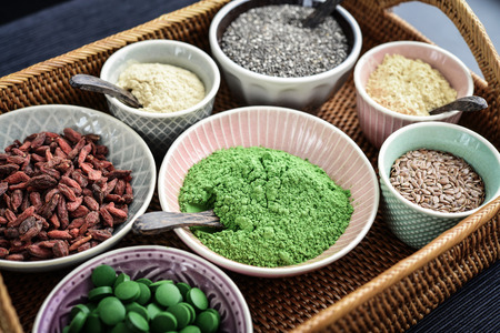 Different super foods in bowls on a rattan tray, top view Stock Photo