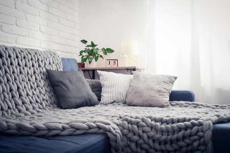 Gray knitted blanket from merino wool on couch with pillows in the interior of the living room