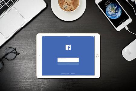 Kiev, Oekraïne - Fabruary 6, 2018: Apple ipad Gold met Facebook-app op het scherm op zwart bureau met Macbook en iphone, bovenaanzicht. Facebook is een onlineservice voor sociale media voor microblogging en netwerken.