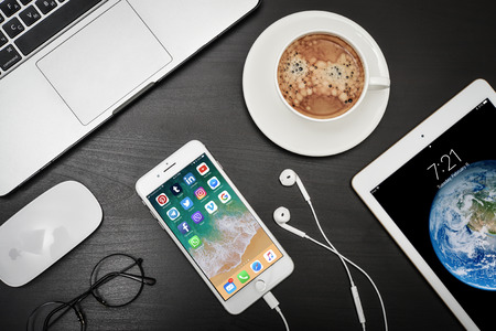 Kyiv, Ukraine - Fabruary 6, 2018: Apple iPhone 8 plus with social network apps on the screen with macbook, ipad, coffee and headphones on black desk, top view. Editorial