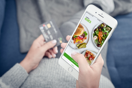 Kyiv, Ukraine - January 24, 2018: Woman using uber eats app on Apple iPhone 8 plus at home for order food delivery