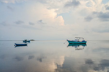 Blue sky with clouds on sunrise, sea and boats on Maldives