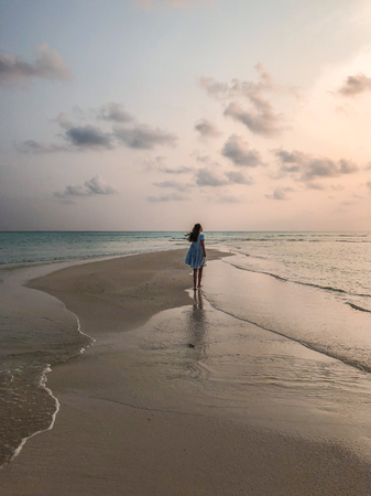 Young girl on the beach at beautyful sunset on Fehendhoo island, Maldives