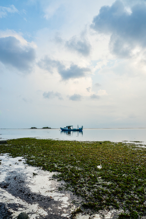 Blue sky with clouds on sunrise, sea and boat on Maldives