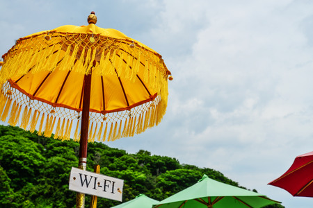 Traditional yellow Hindu umbrella on the beach, Bali, Indonesia. Umbrella in Bali symbol of protection against evil forces.