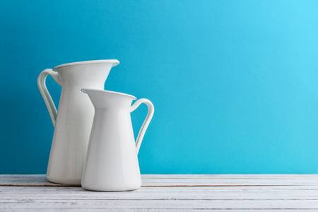 Two white milk enameled jugs on blue background Archivio Fotografico