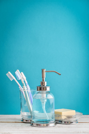 Bathroom set with toothbrushes and soap on blue background