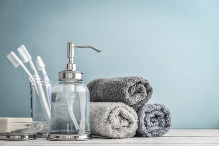 Bathroom set with toothbrushes, towels and soap on blue background 写真素材