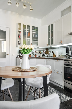 Bouquet of tulips in interior of the kitchen in Scandinavian style with white furniture and a dining table. Archivio Fotografico