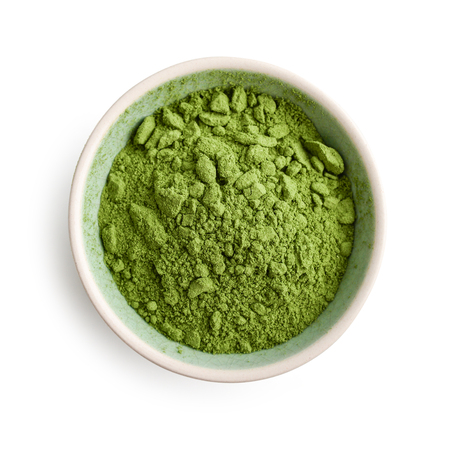 Bowl of matcha powder isolated on white background, top view