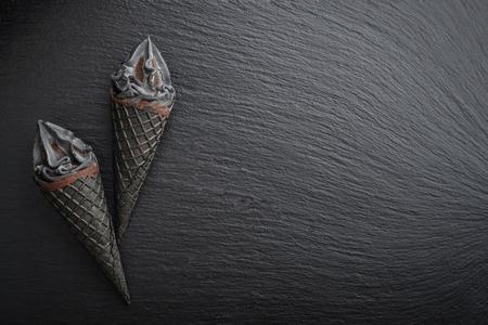 Black ice cream in cone on black slate background, top view Standard-Bild