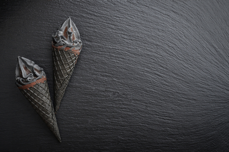 Black ice cream in cone on black slate background, top view Stock Photo