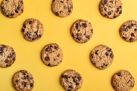 Cookies pattern on the yellow background. Top view of chocolate chip cookies