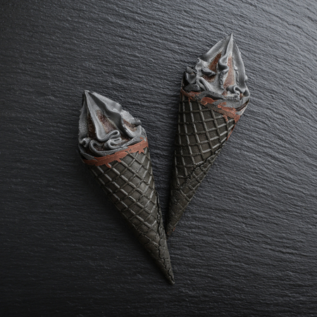 Black ice cream in cone on black slate background, top view