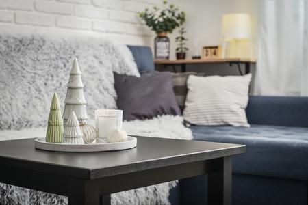 Weihnachtsschmuck mit Kerze auf dem Couchtisch im Wohnzimmer in der Nähe der Couch Nahaufnahme Standard-Bild