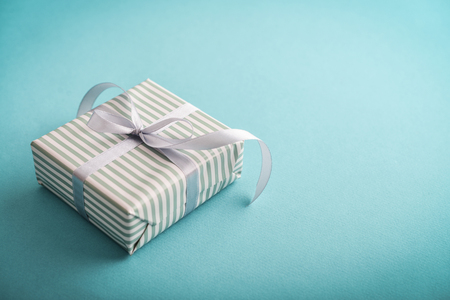 One striped  gift box with grey ribbon on blue background  closeup