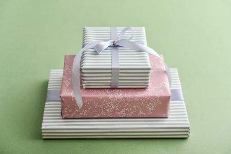 Stack gift boxes with gray ribbon on green background closeup