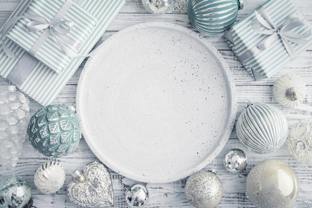 Gift box with different christmas decorations and round tray on white wooden background, top view