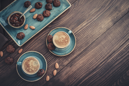 Two cup of coffee and plate with chocolate cookies on wooden background, top view