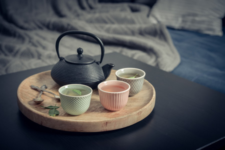 Black iron asian tea set on wooden tray on coffee table in living room closeup