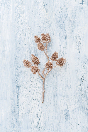 Decorative golden twig with pine cones on white wooden background with crackles, top view