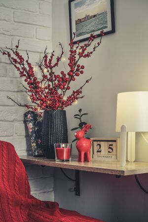 Christmas decor at home. Red toy elk, candle and vase with decorative twigs on shelf closeup