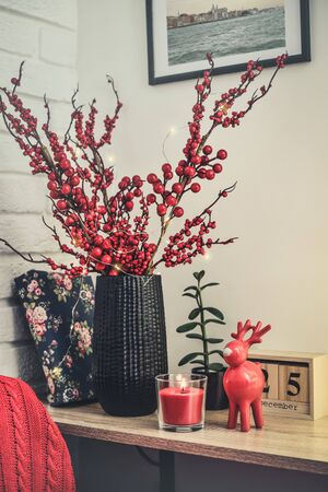 Christmas decor at home. Red toy elk, candle and vase with decorative twigs on shelf closeup. All photos in frames on the wall made by me.