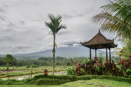 Gazebo with table and chairs by the rice fields with view on Agung volkano on a cloudy day in Bali, Indonesia