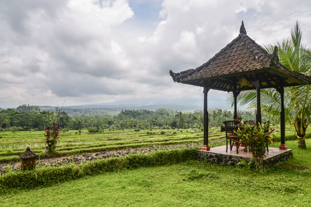 Gazebo with table and chairs by the rice fields on a cloudy day in Bali, Indonesia Stock Photo