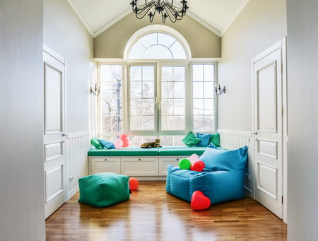 Relax zone in privat house with big window, pouf and bag chair