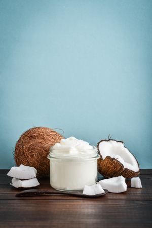 Coconut cream in a glass jar with fresh coconut on a blue background. Healthy vegan food concept.