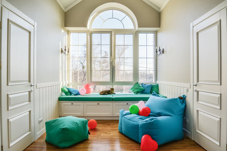 Relax zone in privat house with big window, pouf and bag chair Stock Photo