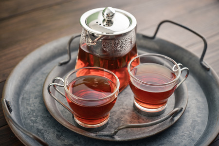 Two glass cup of tea with teapot on round vintage metal tray on wooden background Archivio Fotografico