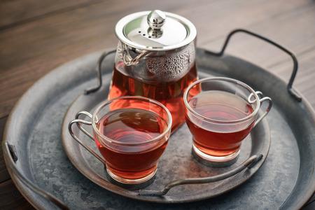 Zwei Glastasse Tee mit Teekanne auf rundem Vintage-Metalltablett auf Holzuntergrund