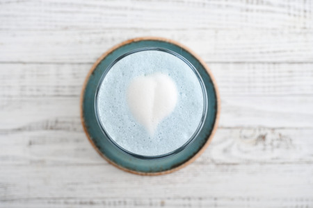 Blue matcha latte in glass on white wooden background, top view Stockfoto