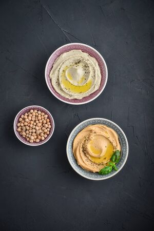 Bowls with different kinds hummus on black background, top view Standard-Bild