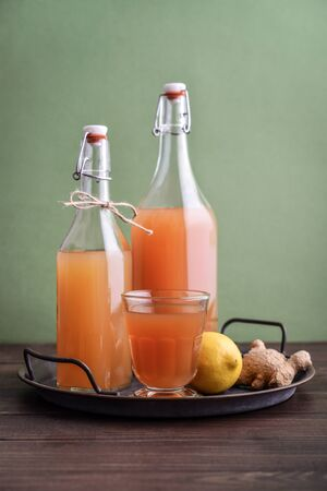 Homemade Fermented Raw Kombucha Tea in glass and bottle with lemon and ginger on green background