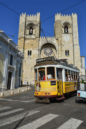 LISBON, PORTUGAL - JULY 2, 2019: A famous yellow tram 28 passing in front of Santa Maria cathedral in Lisbon, Portugal