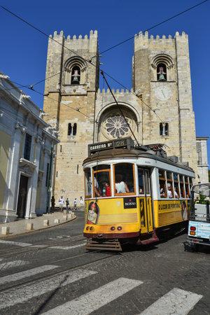 Lissabon, PORTUGAL - 2. JULI 2019: Eine berühmte gelbe Straßenbahn 28, die vor der Kathedrale Santa Maria in Lissabon, Portugal, vorbeifährt?